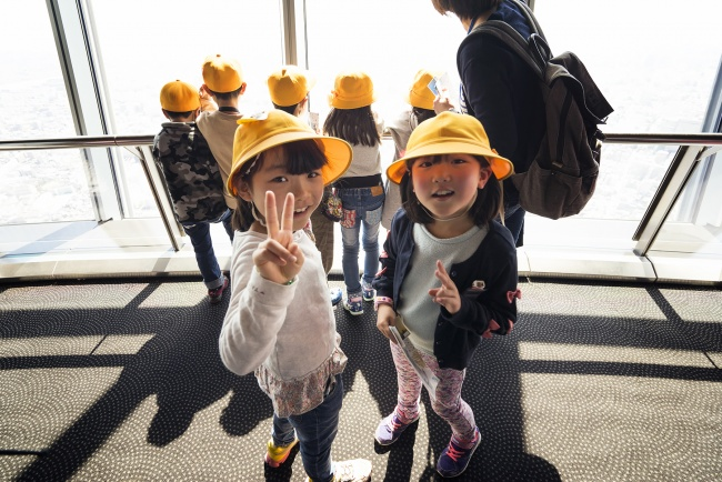 toyko, japan, research, travel, visit, spring, tokyo skytree, tallest building, city, buildings, observation deck, school children, kids, yellow hats, views, creeper, camera, click, photography, photo, decisive moment, lined, asia, peace fingers, smiles, kids, arigatou goziamsu